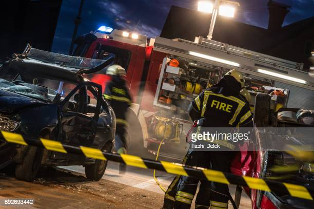 firefighters at a car accident scene - rescue worker stock pictures, royalty-free photos & images