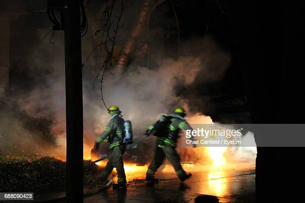 firefighters at work during night - fire protection suit - fotografias e filmes do acervo