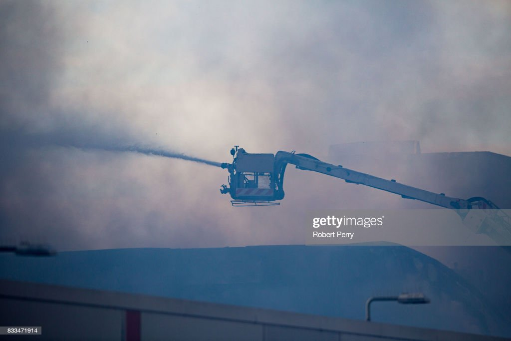 Firefighters attend the scene of a blaze at Blochairn Fruitmarket on August 17, 2017 in Glasgow. The Scottish Fire and Rescue Service (SFRS) are tackling a fire at a warehouse the Blochairn Fruit Market. The fire began at 3.44am and residents have reported hearing two loud explosions. There are no reported casualties or injuries but the SFRS are struggling to get the blaze under control due to low water pressure.