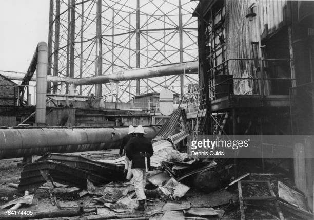 Firefighters attend the scene the morning after a bomb planted by the Provisional Irish Republican Army caused a major fire at the East Greenwich Gas...