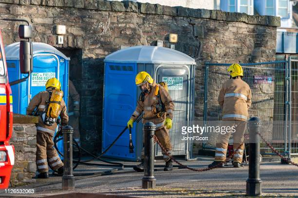firefighters attending a fire - johnfscott stock pictures, royalty-free photos & images
