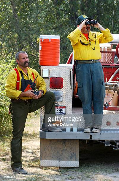 Firefighters Barry Sherman and Dan Ryan of Kootenai County Fire and Rescue watch as a helicopter drops incendiary balls onto trees August 1 2003 on...