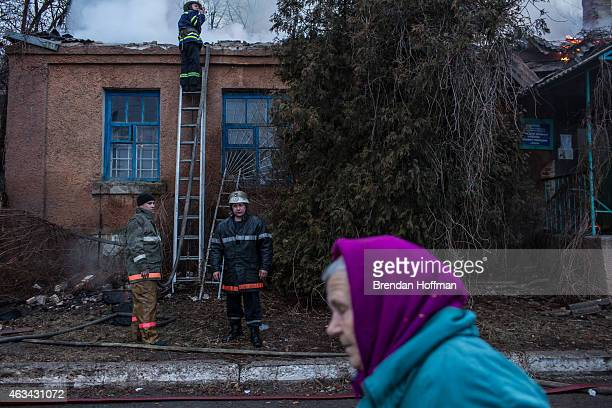 Firefighters battle a blaze at a medical clinic which was hit by artillery on February 14 2015 in Artemivsk Ukraine The clinic was closed and there...