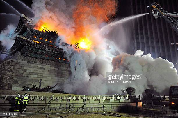 Firefighters battle a blaze at the break down Namdaemun gate one of South Korea's most historic sites in central Seoul on early February 11 2008The...
