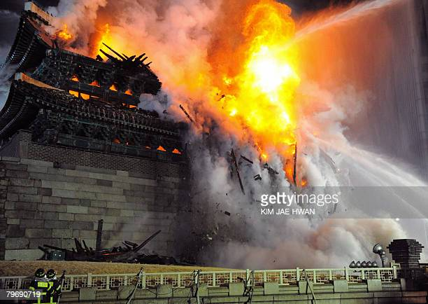 Firefighters battle a blaze at the break down Namdaemun gate one of South Korea's most historic sites in central Seoul on early February 11 2008 The...