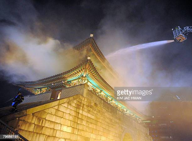 Firefighters battle a blaze at the Namdaemun gate one of South Korea's most historic sites in central Seoul on February 10 2008 The oldest wooden...