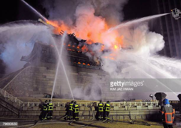 Firefighters battle a blaze at the Namdaemun gate one of South Korea's most historic sites in central Seoul on February 11 2008The oldest wooden...