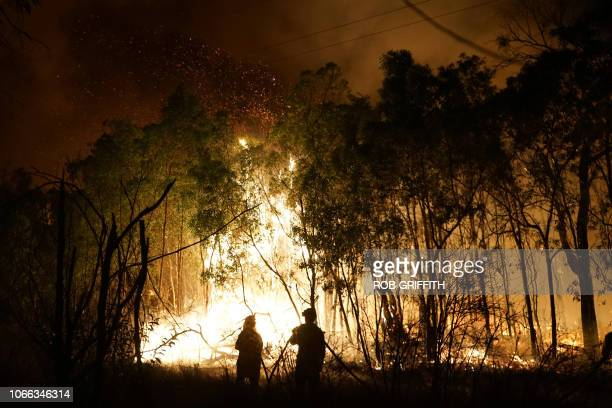 Firefighters battle a blaze on Fingerfield road at the Deepwater National Park area of Queensland on November 29 2018 Thousands of people have been...