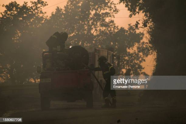 Firefighters battle a blaze that has destroyed thousands of hectares of land on July 25, 2021 in the province of Oristano in Sardinia, Italy....