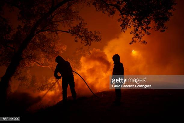 Firefighters battle a forest wildfire next to Vilarinho village near Lousa on October 16 2017 in Coimbra region Portugal At least 36 people have died...