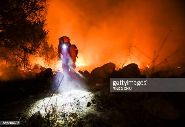 TOPSHOT Firefighters battle a wildfire as it burns along a hillside near homes in Santa Paula California on December 5 2017 Fastmoving windfueled...