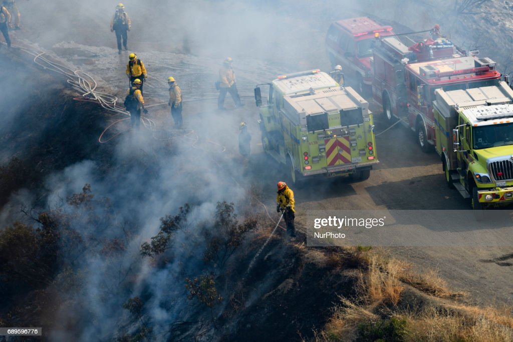 Firefighters battle a wildfire in Mandeville Canyon in Los Angeles, California on May 28, 2017. More than 150 firefighters battle the fire that burns near multi-million dollar homes in the Brentwood neighborhood.
