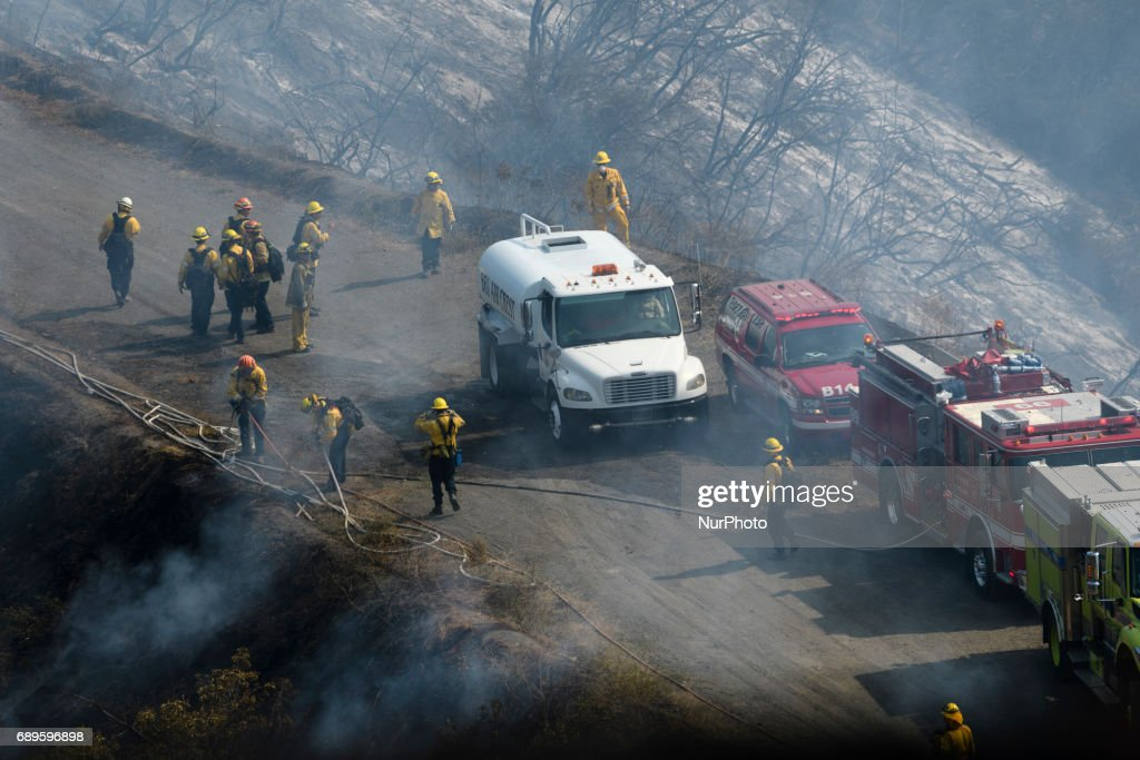 Firefighters battle a wildfire in Mandeville Canyon near the Getty Center in Los Angeles, California on May 28, 2017. More than 150 firefighters battle the fire that burns near multi-million dollar homes in the Brentwood neighborhood.