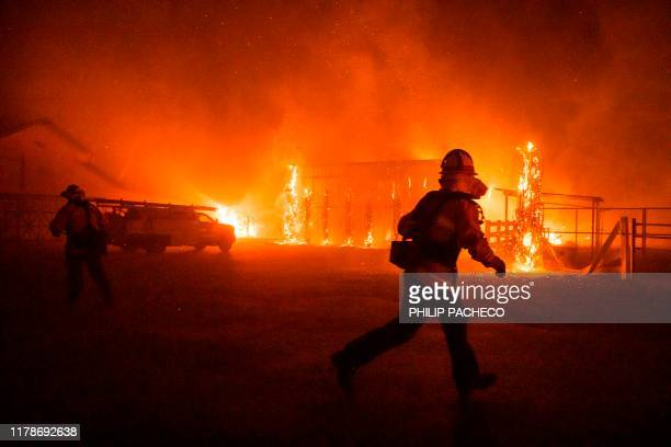Firefighters battle a winddriven fire burning structures on a farm during the Kincade fire in Windsor California on October 27 2019 California's...