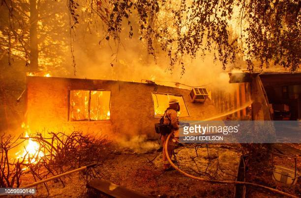 Firefighters battle flames at a burning apartment complex in Paradise, north of Sacramento, California on November 09, 2018. - A rapidly spreading,...