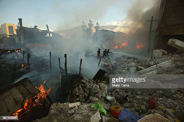 Firefighters battle one of several suspicious blazes in the Iron Market area January 29, 2010 in Port-au-Prince, Haiti. Hundreds of thousands remain...