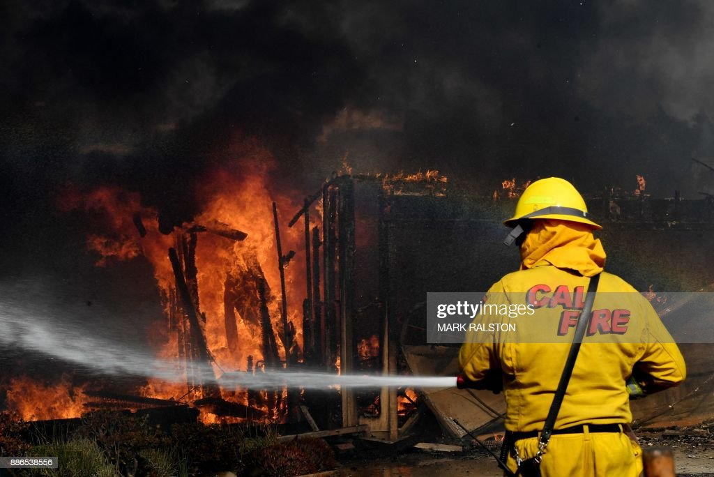Firefighters battle strong winds as they try to save a house during the Thomas wildfire in Ventura, California on December 5, 2017. Firefighters battled a wind-whipped brush fire in southern California that has left at least one person dead, destroyed more than 150 homes and businesses and forced tens of thousands to flee. /