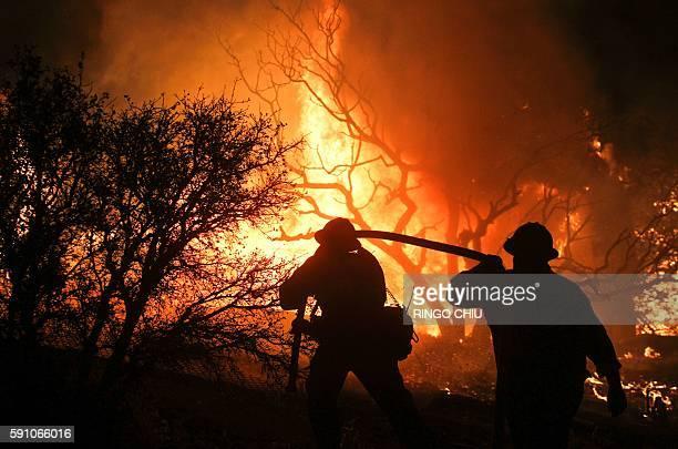 Firefighters battle the Blue Cut wildfire burning near Cajon Pass north of San Bernardino California on August 16 2016 A rapidly spreading fire...