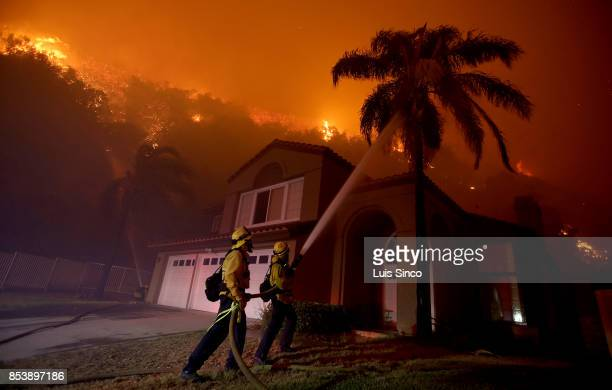 Firefighters battle the Canyon Fire as flames threaten a neighborhood on September 25 2017 in Corona California The fire charred about 1500 acres by...