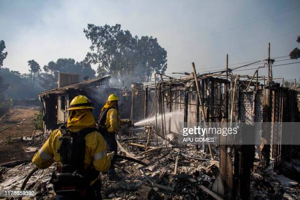 Firefighters battle the Getty Fire in houses on fire in Brentwood California on October 28 2019 A wildfire broke out early Monday near the renowned...