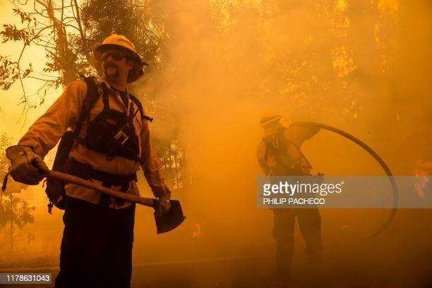 Firefighters battle the Kincade Fire along Chalk Hill Road in Healdsburg California on October 27 2019 Powerful winds were fanning wildfires in...