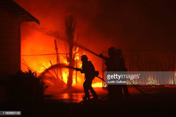 Firefighters battle the Kincade Fire as it burns a barn on October 27 2019 in Santa Rosa California Fueled by high winds the Kincade Fire has burned...