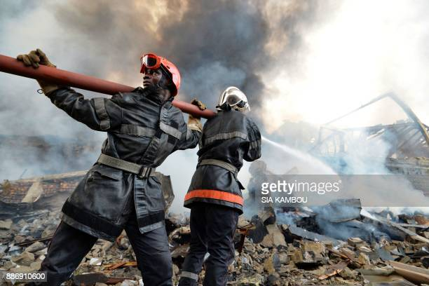 TOPSHOT Firefighters battle the remnants of a fire at the Drocolor paint factory on December 6 2017 in Abidjan A huge fire ripped through a paint...