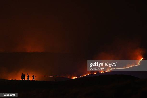 Firefighters battle to control the flames from a moor fire on Marsden moor, near Huddersfield in northern England on April 25, 2021.
