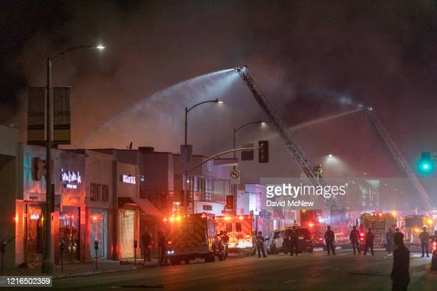 Firefighters battle to put out burning buildings on Melrose Avenue in the Fairfax District during demonstrations following the death of George Floyd...