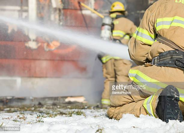 firefighters battling winter house fire - extinguishing stock pictures, royalty-free photos & images