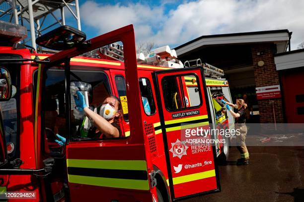 Firefighters Becky Wallis and Penny Ewbank use antibacterial wipes to clean the fire engine at Station 08 following a call to a put out a wildfire in...