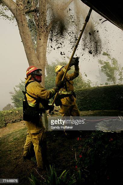Firefighters Bill Clark and Sean Threlfall pull debris from a gutter as they try to save a home from burning down October 22 2007 in Poway California...