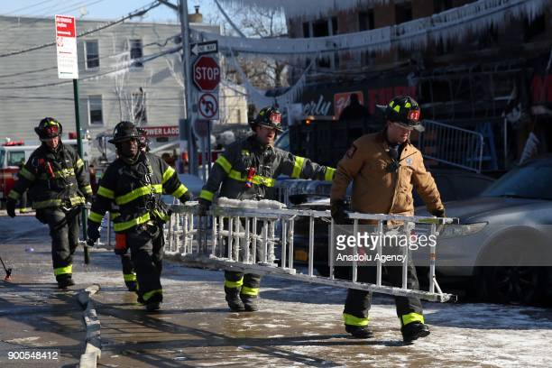 Firefighters carry a ladder as they continue works to extinguish a fire that broke out at an apartment leaving 16 injured according to initial...
