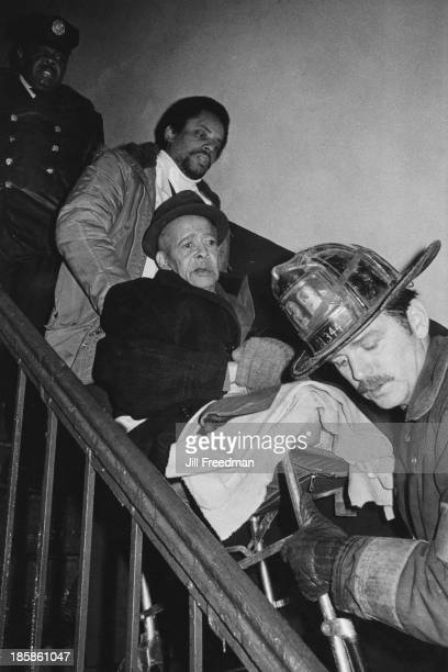 Firefighters carry a legless man down the stairs inside a burning building in Harlem New York City circa 1976