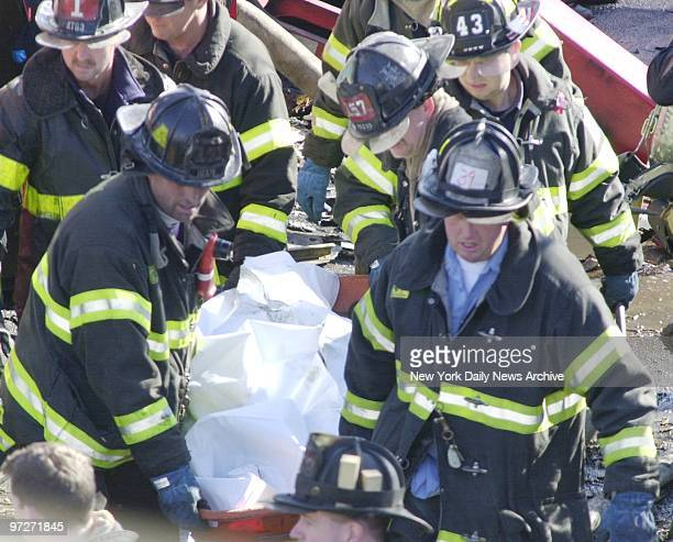 Firefighters carry a shrouded body from one of the smoldering crash sites of American Airlines flight 587 at Beach 131 and Newport Ave after it...
