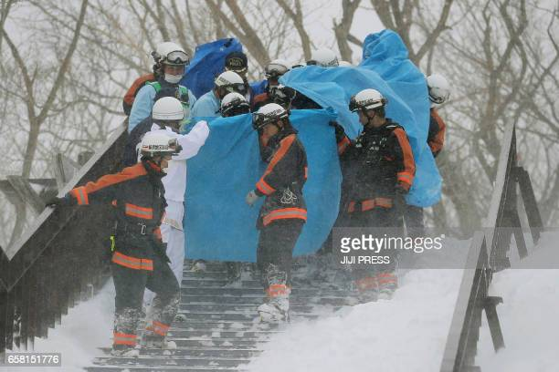 Firefighters carry a survivor they rescued from the site of an avalanche in Nasu town Tochigi prefecture on March 27 2017 Eight high school students...