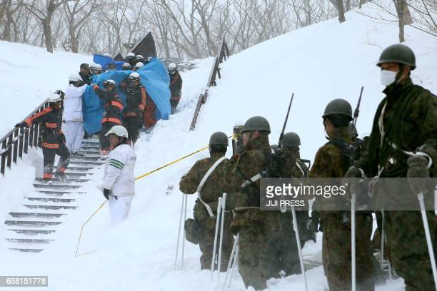 Firefighters carry a survivor they rescued from the site of an avalanche in Nasu town Tochigi prefecture on March 27 while Self Defense Force...