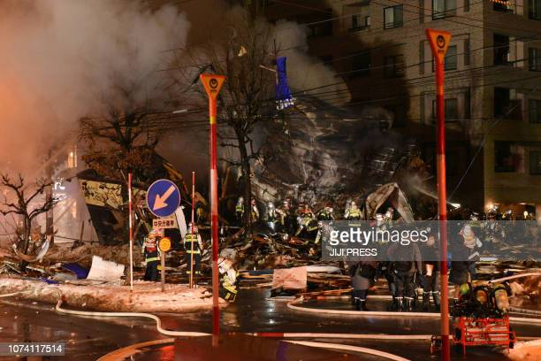 TOPSHOT Firefighters carry on rescue works after an explosion at a restaurant in Sapporo in the northern Hokkaido prefecture on December 16 2018...