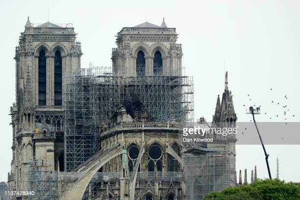 Firefighters carry out inspections on the damaged roof of NotreDame Cathedral following a major fire yesterday on April 16 2019 in Paris France A...