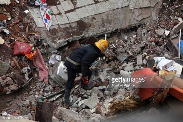 Firefighters carry out search and rescue work for the survivors in the debris at site of a collapsed building in Mumbai on July 25, 2017. At least...