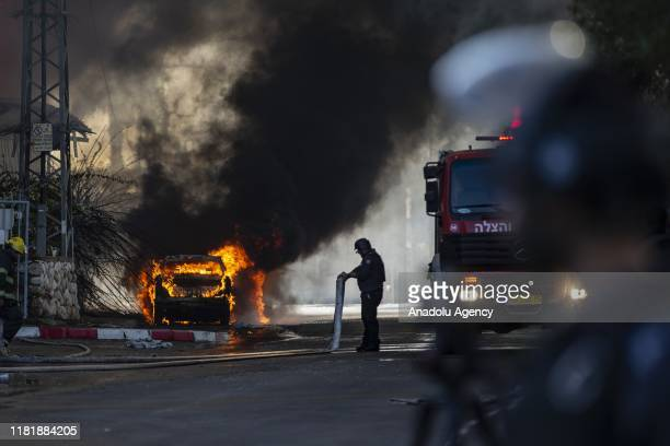 Firefighters carry out works to extinguish the fire that broke out after rockets fired into southern Israel hit a textile factory in response to the...