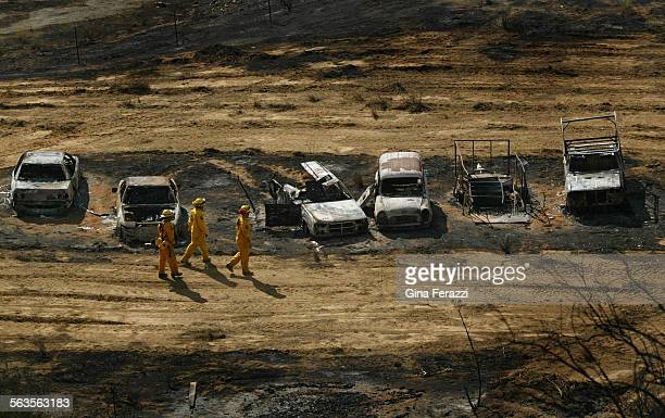 CDF firefighters check on smoldering cars destroyed by the El Cerrito fire Wednesday in the Temescal Canyon area north of Lake Elsinore