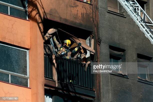 Firefighters check the damage after extinguishing a fire that broke out at an apartment building in Badalona near Barcelona on January 5 2019 At...