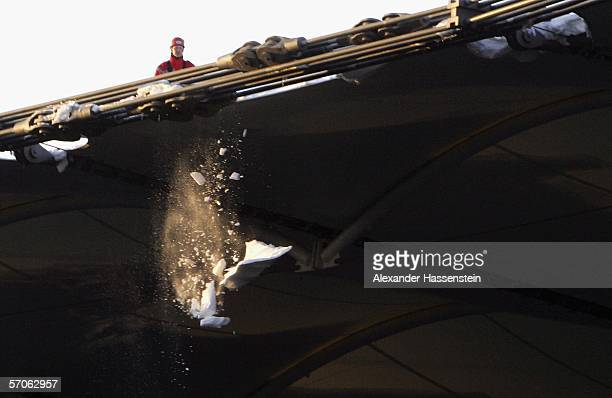 Firefighters clean the stadium roof of snow before the Bundesliga match between Hamburger SV and 1 FC Kaiserslautern at the AOL Arena on March 12...