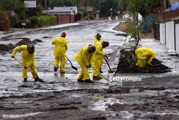 Firefighters clear debris from a mudslide in Los Angeles California on January 9 2018 The deadly rain storm claimed the lives of 13 people in Santa...