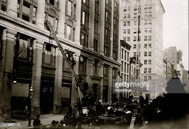 Firefighters climb an extension ladder up to a building window during a fire drill exercise at the National Cloak and Suit Company Seventh Avenue New...
