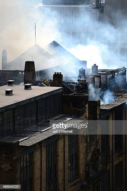 Firefighters climb onto the roof of the Glasgow School of Art Charles Rennie Mackintosh Building to attempt to put out a fire on May 23 2014 in...