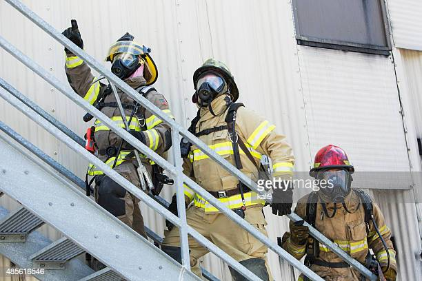 firefighters climbing stairs outside industrial building - zuurstofmasker stockfoto's en -beelden