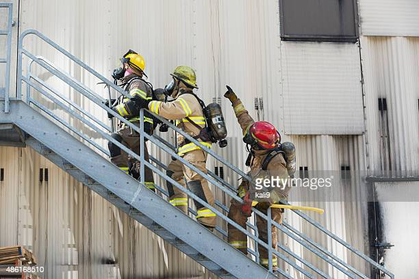 firefighters climbing stairs outside industrial building - emergency first response stock photos and pictures