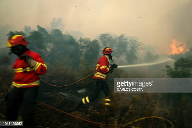 Firefighters combat a wildfire close to Monchique in the Portuguese Algarve, on August 8, 2018. - Wildfires scorched across Portugal's southern...
